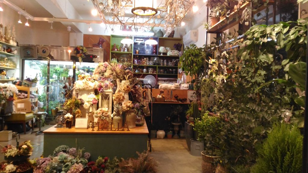 A flower shop in the market.  What else can you see?